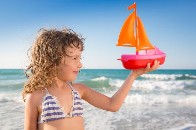 Счастливый ребенок играет с игрушечной парусной лодкой на фоне синего моря и неба улыбающийся ребенок на пляже концепция путешествий и приключений