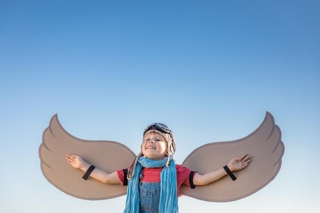 Счастливый ребенок играет с игрушечными крыльями на фоне голубого неба