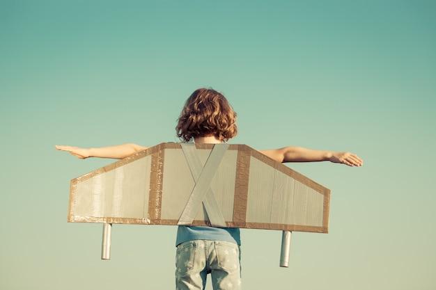 Счастливый ребенок, играя с игрушечными крыльями на фоне летнего неба. ретро тонированное