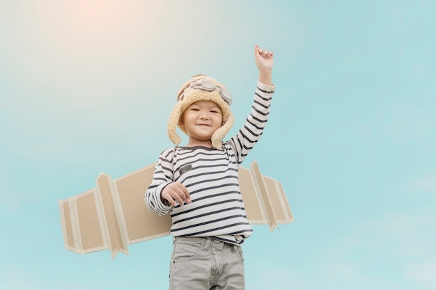 Happy child playing with toy wings against summer sky background.