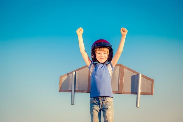 Счастливый ребенок играет с игрушечными крыльями на фоне летнего неба