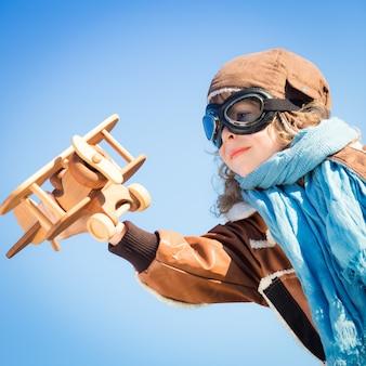 겨울 하늘 배경에 장난감 나무 비행기를 가지고 노는 행복한 아이