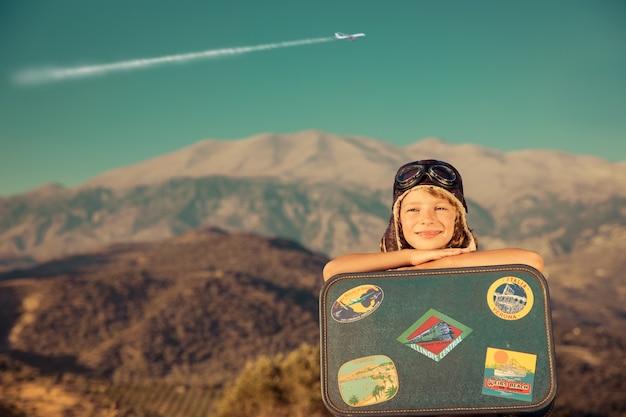 하늘 배경에 산과 비행기에 대한 빈티지 가방을 가지고 노는 행복한 아이