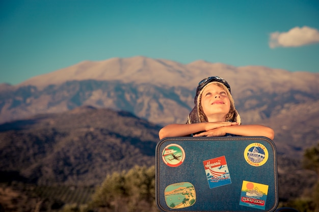 산과 푸른 하늘 배경에 빈티지 가방을 가지고 노는 행복한 아이