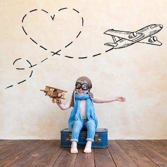 Happy child playing with vintage wooden airplane at home.