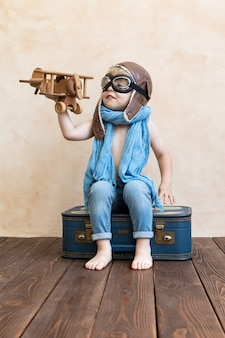 Happy child playing with vintage wooden airplane.