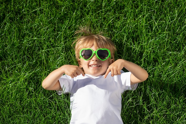 Happy child points fingers at t-shirt. funny kid against spring green background. ecology and healthy lifestyle concept.
