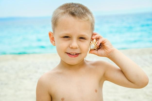 Счастливый детский портрет, играющий на берегу моря