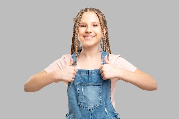Счастливый детский портрет. как жест. веселая девушка показывает палец вверх улыбается