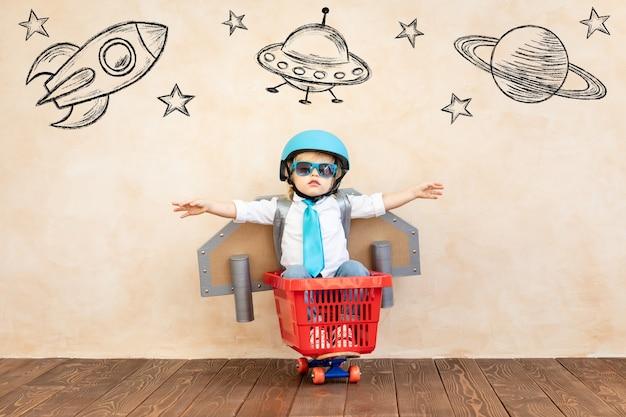 Счастливый ребенок притворяется космонавтом.