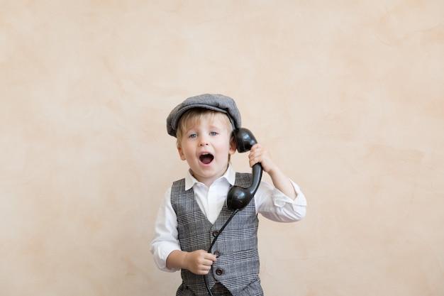 幸せな子供はビジネスマンのふりをします。電話で話している面白い子供。ビジネス交渉の概念
