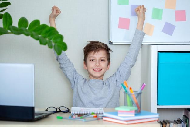 幸せな子供は手を挙げて、自宅のコンピューターで宿題をしました。ホーム遠隔オンライン教育。