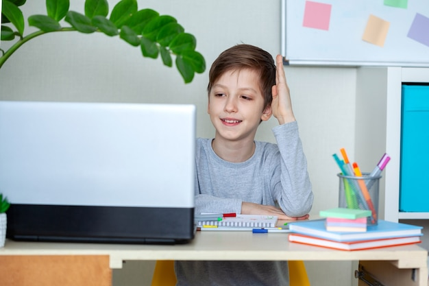 Happy child raised his hands, doing homework at the computer at home. home distant online education.