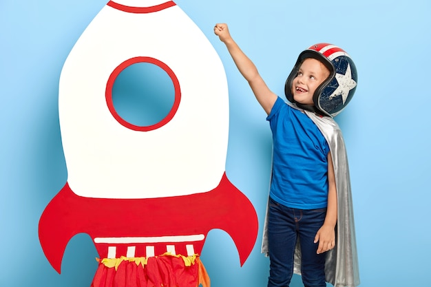 Happy child raises arm near paper carton toy rocket, wants to fly into space
