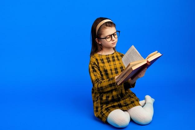 책을 읽고 파란색 벽에 앉아 행복 한 아이