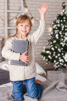 Happy child reading a book at christmas