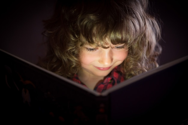 Happy child reading magic book