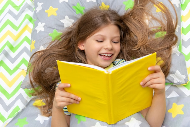 A happy child reads a book in bed before going to bed.