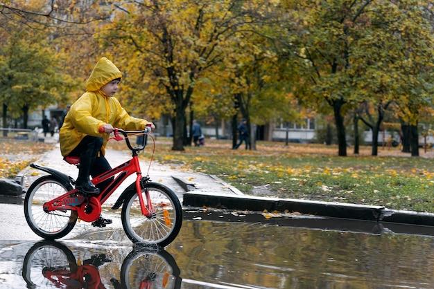 Счастливый ребенок едет на велосипеде под дождем и по лужам. мальчик в желтом плаще катается по лужам.