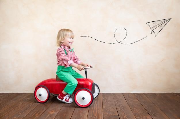 ヴィンテージカーに乗って幸せな子。家で楽しんでいる子供。想像力と子供の頃の概念
