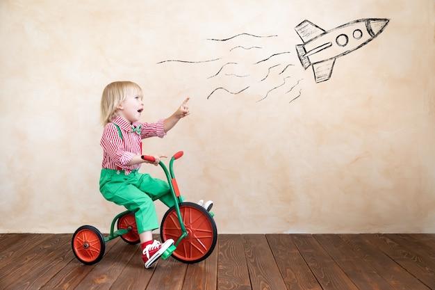 ヴィンテージ三輪車に乗って幸せな子。家で楽しんでいる子供。想像力と子供の頃の概念