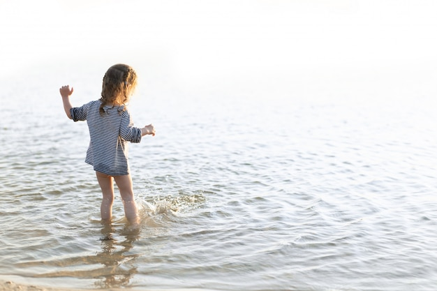 Happy child running and jumping in the waves during summer vacation. holiday on sea or ocean coast for family with young children. kids play at the sea. little girl do splases with legs.