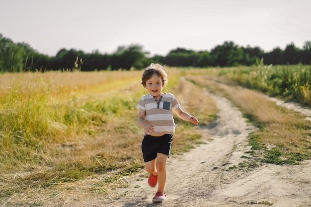 自然の中で夏に牧草地で走っている幸せな子。