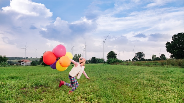 Happy child running with balloons