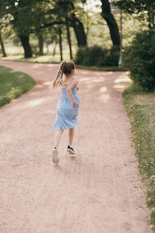 A happy child runs through the park. a girl in a blue dress rests in the park. a happy child is genuinely happy. high quality photo