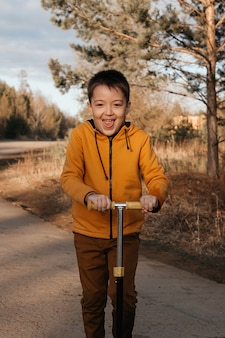 Happy child on a scooter in the park. children learn to ride on roller boards. active recreation for children on a safe residential street. active sports for preschool children.