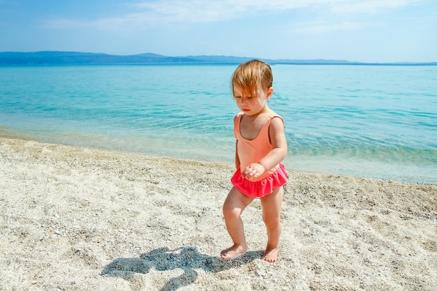 Happy child at sea in greece plays in nature