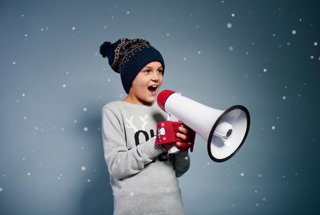 Счастливый ребенок кричит в мегафон