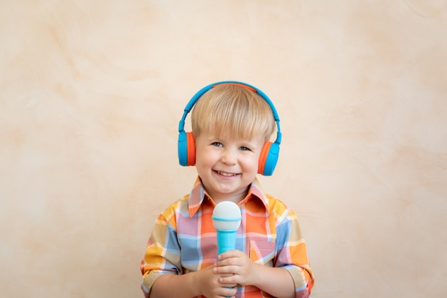 Happy child singing a song. funny kid playing at home