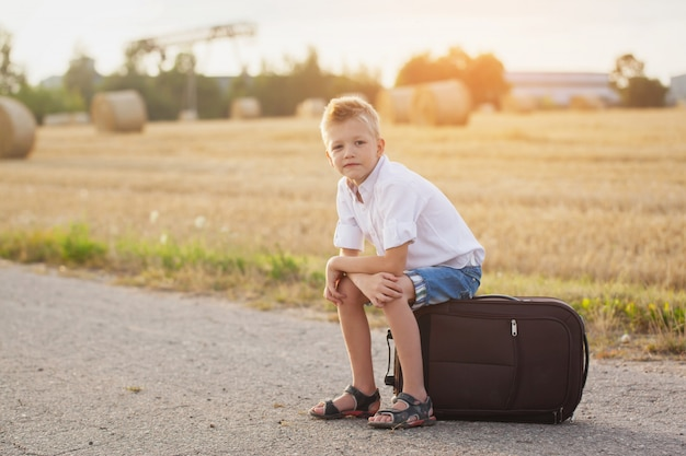 The happy child sits on a suitcase in the summer sunny day, the traveler