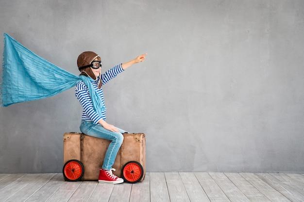 회색 배경에 슈퍼히어로 망토를 쓴 조종사처럼 옷을 입고 낡은 가방에 앉아 있는 행복한 아이