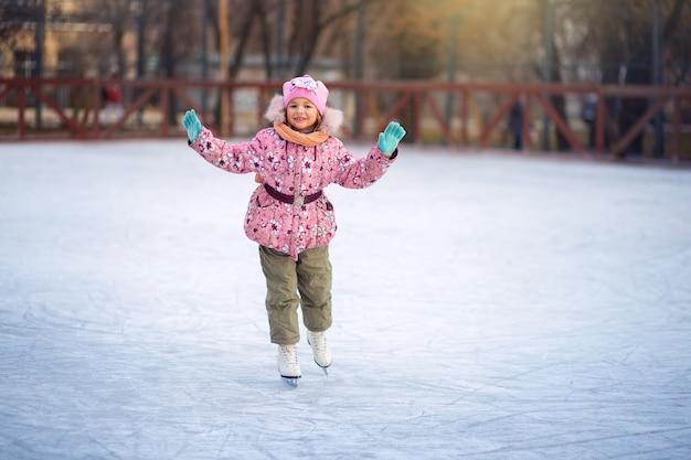Happy child skates on ice rink in winter