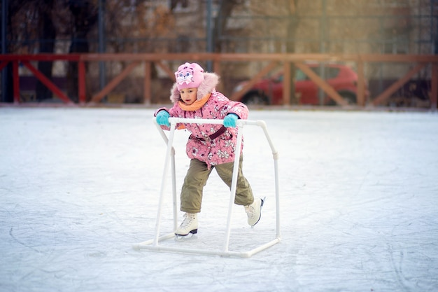Happy child skates on an ice rink with a special support