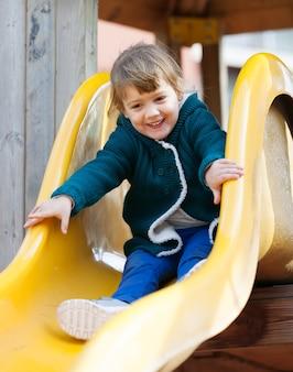 Bambino felice sulla diapositiva al parco giochi