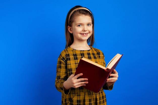 웃 고 파란색 벽에 책을 들고 행복 한 아이