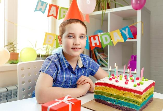 Счастливый ребенок улыбается в шапке дня рождения. именинный торт со свечами. партия