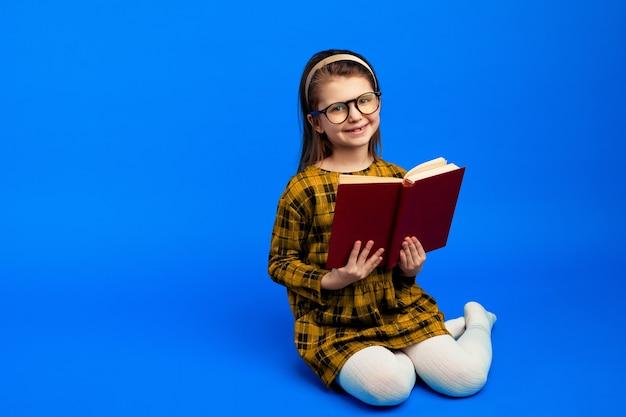 파란색 벽에 앉아 책을 읽는 동안 웃고 행복 한 아이