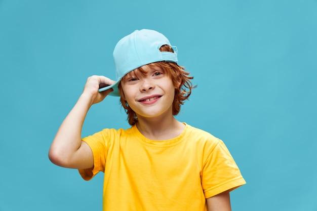 Счастливый ребенок поправляет шапку на голове и рыжие волосы я