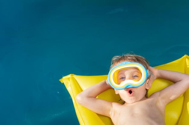 Счастливый ребенок плавание в бассейне. малыш веселится на летних каникулах. концепция здорового образа жизни