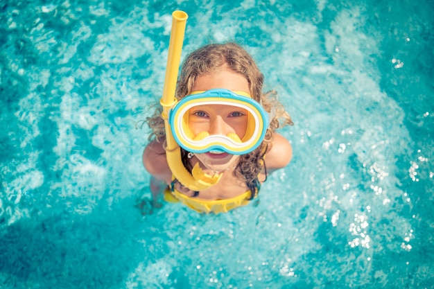 Happy child in swimming pool. top view portrait