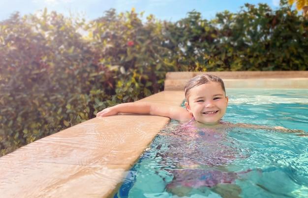 Счастливый ребенок плавает в бассейне