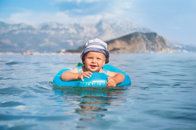 A happy child swims in a swimming ring in the adriatic sea