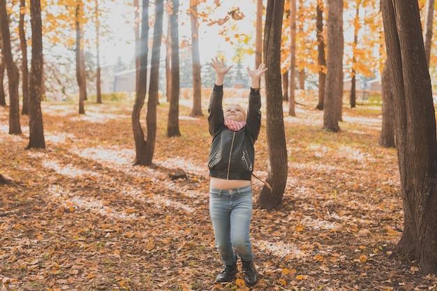 落ち葉を投げる幸せな子供は、秋の公園で遊んでいます。秋の公園を歩いている子供たち。