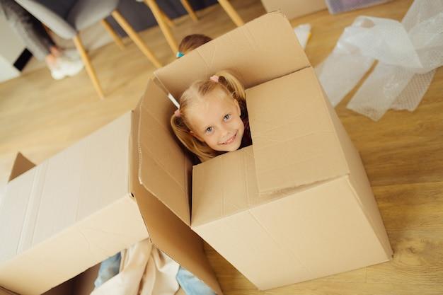Счастливый ребенок. вид сверху довольно симпатичной девушки сидя в коробке