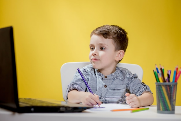 노란색에 숙제를 하 고 디지털 노트북을 사용 하여 행복 한 아이. 사회적 거리두기, e- 러닝 온라인 교육.