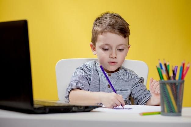 Счастливый ребенок с помощью цифрового ноутбука делает домашнее задание